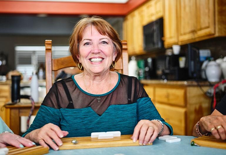 Frau sitzt am Tisch und lächelt