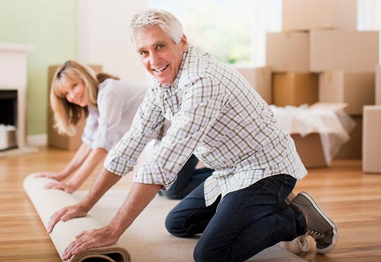 Ehepaar rollt einen Teppich aus